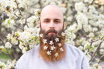 Portrait of hipster with white tree blossoms in his beard - p300m1581052 von VITTA GALLERY