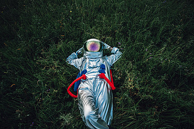 Spaceman exploring nature, relaxing in meadow - p300m2030502 by Vasily Pindyurin
