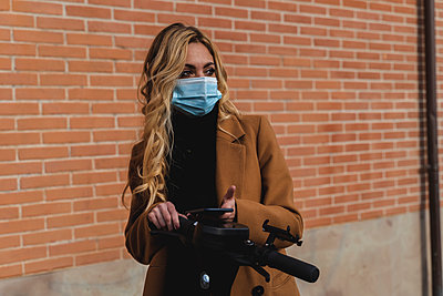 Young woman in protective face mask standing with electric push scooter against brick wall - p300m2251285 by Francesco Morandini