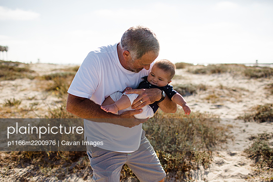 Grandfather Cradling Grandson While Standing on Beach - p1166m2200976 by Cavan Images