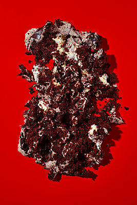 The remains of a piece of cake on a red background - p1423m2164203 by JUAN MOYANO