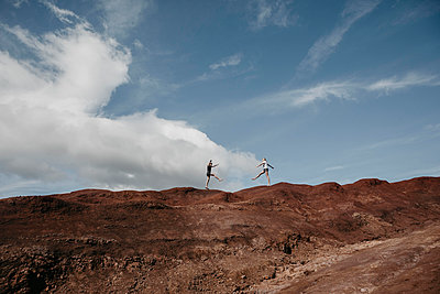 Distant view of friends practicing yoga on dramatic landscape at Waimea Canyon, Kauai, Hawaii, USA - p300m2199203 by letizia haessig photography