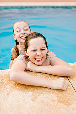 Cheerful siblings playing at poolside - p300m2281384 by Lightsy Studio