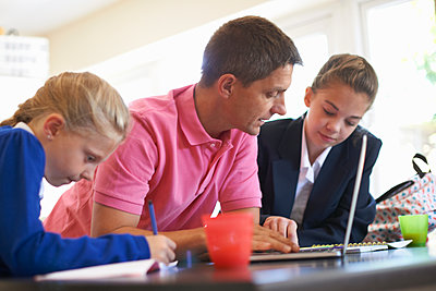 Father helping daughters with homework at kitchen counter - p429m1504612 by Peter Muller