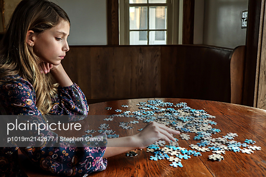 Girl doing puzzle - p1019m2142877 by Stephen Carroll
