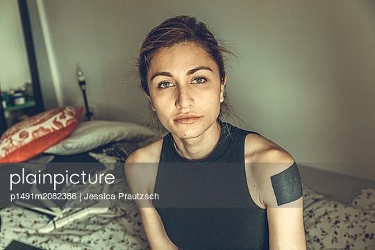 Frau sitzt auf dem Bett und blickt in die Kamera - p1491m2082386 von Jessica Prautzsch