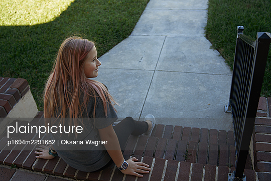 Rear View of a smiling girl sitting on brick steps of the front porch  - p1694m2291682 by Oksana Wagner