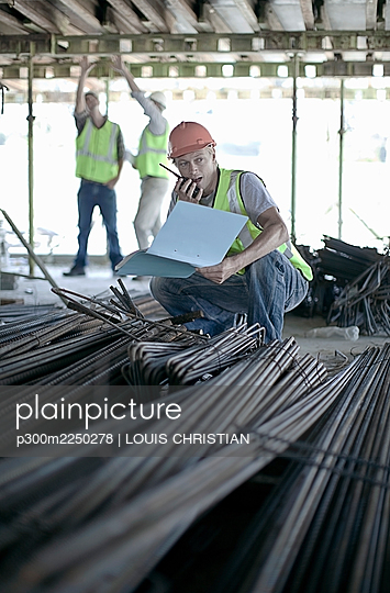 Male construction worker talking on walkie-talkie while coworkers discussing in background at construction site - p300m2250278 by LOUIS CHRISTIAN