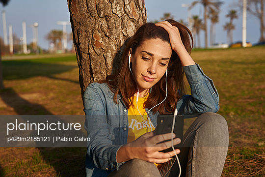 A woman sitting against a tree trunk listening to something through earphones and a mobile phone. - p429m2185121 by Pablo Calvo