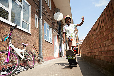 Portrait carefree boy skateboarding in sunny apartment alleyway - p1023m2238489 by Himalayan Pics