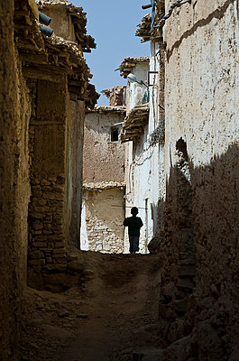 Silhouetted boy playing in narrow alley in Berber village - p1072m1056675 by chinch gryniewicz