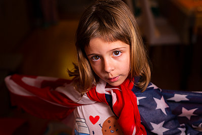 6-year-old girl dancing wrapped in the U.S. flag - p1166m2193954 by Cavan Images