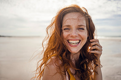 Portrait of a redheaded woman, laughing happily on the beach - p300m2023529 von Kniel Synnatzschke
