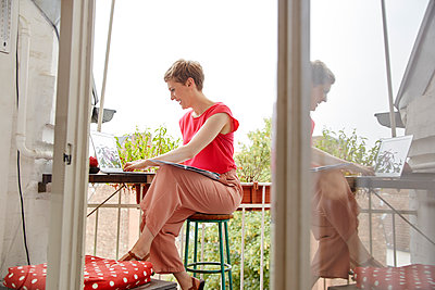 Happy woman sitting on balcony at home with laptop and map - p300m2059535 von Rainer Holz