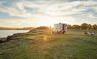Chile, Talca, Rio Maule, camper at lake with family having dinner at sunset - p300m2070737 by Stefan Schütz