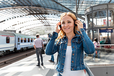 Smiling woman listening to music with headphones at the station, Berlin, Germany - p300m2156839 by William Perugini