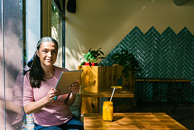 Mature woman holding digital tablet while leaning on window at cafe - p300m2227353 by Xavier Lorenzo