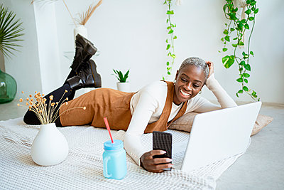 Spain, Valencian Community, Valencia. Lifestyle Afro-American woman working with computer and tablet at home. - p300m2276372 von Rafa Cortés