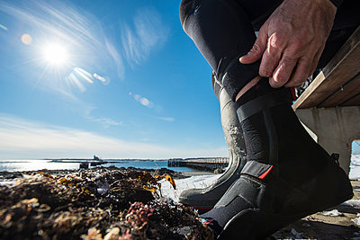 A Paddleboarder Getting Suited Up For A Winter Paddle In Maine - p343m1223787 by Joe Klementovich