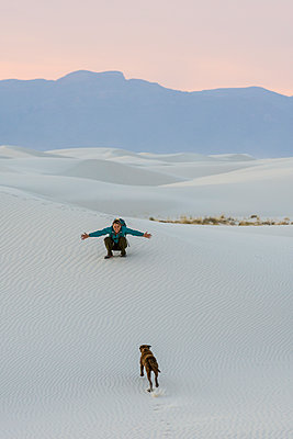 Woman and dog hiking in White Sands National Monument, Alamogordo, New Mexico, USA - p343m2002799 by Kennan Harvey