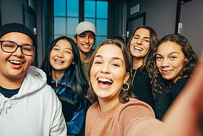 Cheerful teenage classmates taking selfie in corridor - p426m2127617 by Maskot