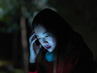 Young woman outdoors at night, using mobile phone, face illuminated - p429m1052747 by Elke Meitzel