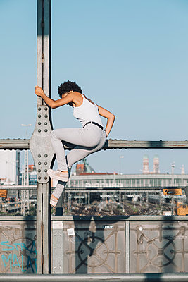 Female teenager climbing on bridge - p728m2038822 by Peter Nitsch