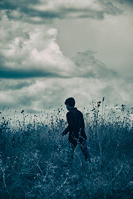 Boy walking away in the field  - p794m1123658 by Mohamad Itani