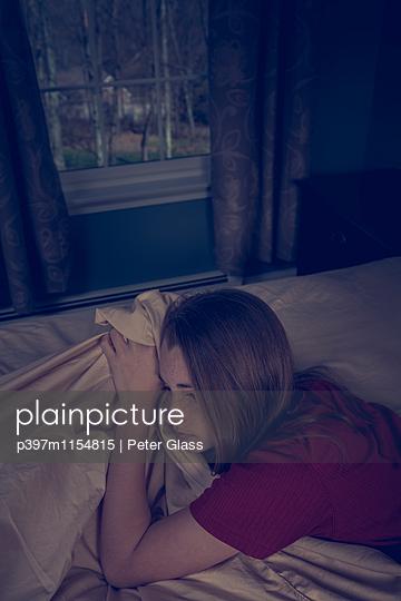 Weiblicher Teenager liegt auf einem Bett - p397m1154815 von Peter Glass