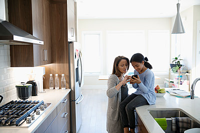 Mother and daughter using smart phone in kitchen - p1192m2094363 by Hero Images