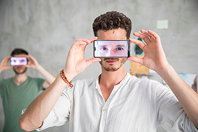 Two men are holding their smartphones with eyes on the display  - p276m2110764 by plainpicture