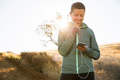Mature female runner on sunlit hill choosing smartphone music - p429m1103252 by Ian Spanier
