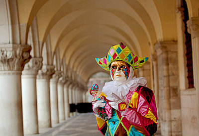 Venice, Veneto, Italy, Mask under the arches of the Palazzo dei Dogi on Piazza San Marco during carnival. - p652m716789 by Ken Scicluna