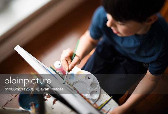 High angle close up of young boy painting on a canvas on an easel. - p1166m2112532 by Cavan Images