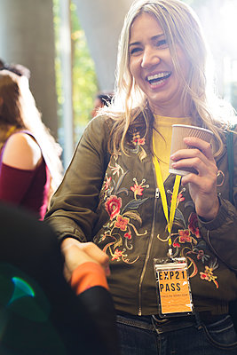 Smiling woman with coffee at conference - p1023m1583830 by Martin Barraud