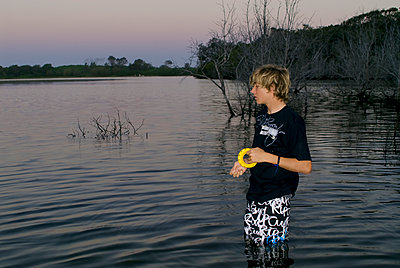 Boy fishing in creek in the evening - p1125m2013969 by jonlove