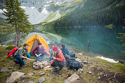 Friends hanging out around campfire at remote lakeside - p1192m1184081 by Hero Images