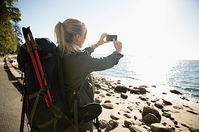 Blonde woman with hiking backpack photographing sunny ocean beach with camera phone - p1192m1512010 by Hero Images