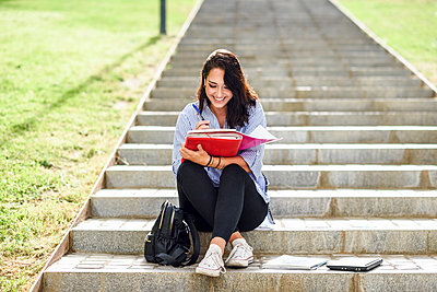 Smiling student sitting on stairs outdoors taking notes in a notebook - p300m2060221 von Javier Sánchez Mingorance