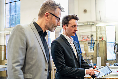 Two businessmen with tablet in a factory - p300m2102812 by Daniel Ingold