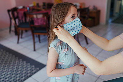 Mother's hands tries mask on daughter's face in living room - p300m2243256 by Oxana Guryanova