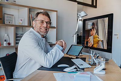 Smiling doctor with patient over video call on computer at doctor's office - p300m2266897 by Mareen Fischinger