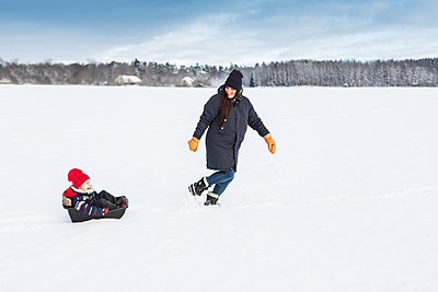 Mother playing with child in snow in Sweden - p352m1536594 by Calle Artmark