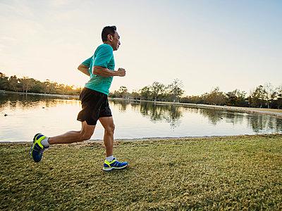 Older Chinese man running in park - p555m1305456 by Erik Isakson