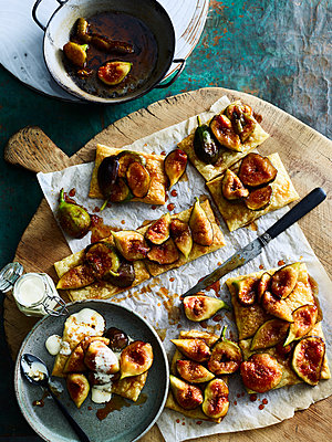 Pieces of figs on crackers served on cutting board - p924m2136525 by BRETT STEVENS