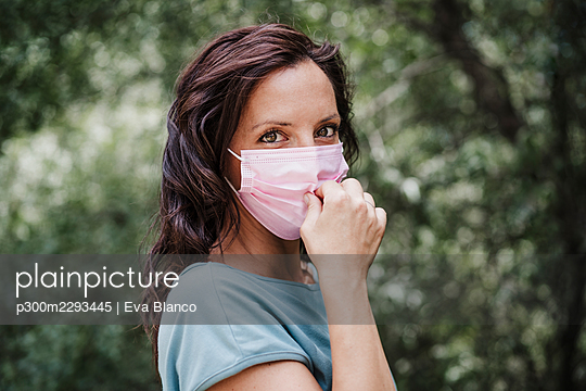 Woman wearing protective face mask in forest during COVID-19 - p300m2293445 by Eva Blanco