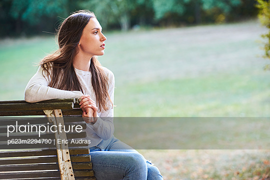 Thoughtful young woman sitting on bench in park - p623m2294790 by Eric Audras
