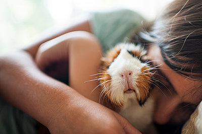 Close-up of girl embracing guinea pig while lying at home - p1166m2112432 by Cavan Images