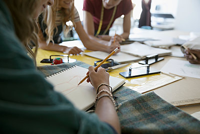 Fashion design students talking, sketching at workbench in studio - p1192m1493329 by Hero Images