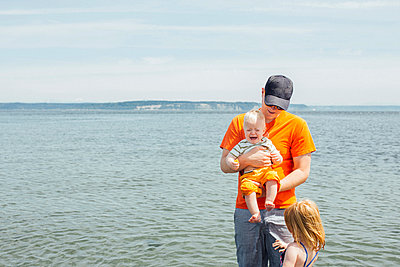 Father with Young Children Holding Crying Baby at the Beach - p1238m1042067 by Amanda Voelker